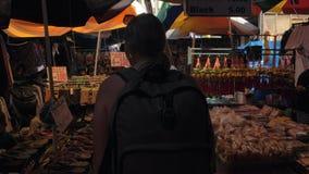 Манила, Филиппины - 26-ое ноября 2018: Кавказский женский путешественник с рюкзаком идя на азиатский уличный рынок внутри акции видеоматериалы