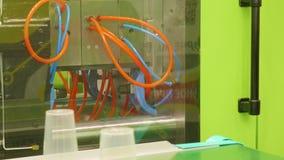 Манипулятор кладет пластиковые чашки на линию машины для делать пластиковые diches сток-видео