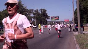 Марафонцы в белой футболке и черные шорты, в зеленых крышках и солнечных очках, который побежали вдоль бульвара, на асфальте сток-видео