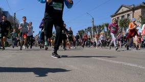 Марафон города Толпа бегунов людей, который и спортсменов побежали вдоль дороги в городе видеоматериал