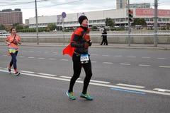 Марафон Москвы Человек бегуна в черном и красном костюме Стоковые Фото