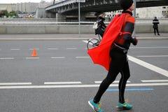 Марафон Москвы Человек бегуна в черном и красном костюме Стоковое Фото