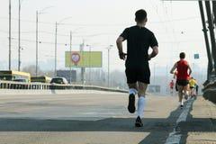 Марафон через дороги города E Гонка марафона идущая, ноги людей на дороге города стоковая фотография rf