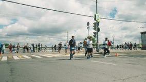 Марафон Sportive людей идущий вокруг металла ограждая на перекрестке города акции видеоматериалы