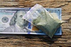 Марихуана в пакете и долларовая банкнота 100 на деревянном столе Стоковое Изображение