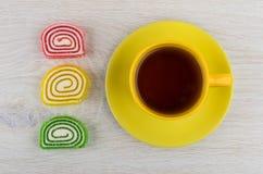 Мармелады красных, желтых, зеленых цветов и чашки чаю Стоковые Изображения RF