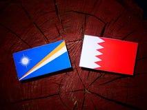 Маршалловы Острова сигнализируют с бахрейнским флагом на изоляте пня дерева Стоковое Фото