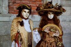 Маска и костюм красочной масленицы золото-коричневая на традиционном фестивале в Венеции, Италии стоковая фотография