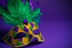 Маска марди Гра или Carnivale на фиолетовой предпосылке Стоковое Изображение