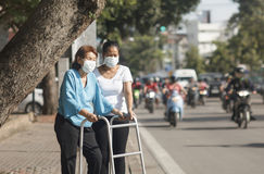 Маска пожилой женщины нося для защищает загрязнение воздуха Стоковые Изображения