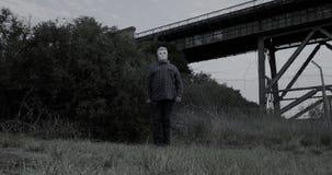 Маска хеллоуина страшного человека нося белая поворачивает прогулки медленно прочь страшный
