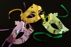 3 маски масленицы на темной предпосылке стоковые фото