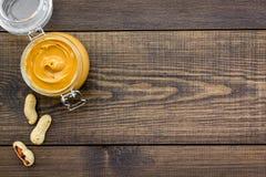 Масло гайки в стеклянном опарнике около арахиса на темном деревянном космосе экземпляра взгляд сверху предпосылки Стоковое фото RF