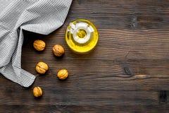 Масло как косметики Масло грецкого ореха около грецкого ореха в ореховой скорлупе на темном деревянном copyspace взгляд сверху пр Стоковое фото RF