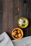 Масло как косметики Масло грецкого ореха около грецкого ореха в ореховой скорлупе на темном деревянном copyspace взгляд сверху пр Стоковые Фото