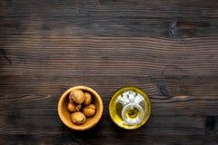 Масло как косметики Масло грецкого ореха около грецкого ореха в ореховой скорлупе на темном деревянном космосе экземпляра взгляд  Стоковые Фото