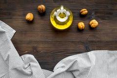 Масло как косметики Масло грецкого ореха около грецкого ореха в ореховой скорлупе на темном деревянном космосе экземпляра взгляд  Стоковые Фотографии RF