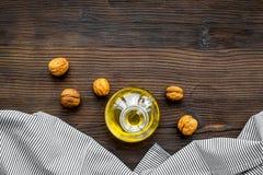 Масло как косметики Масло грецкого ореха около грецкого ореха в ореховой скорлупе на темном деревянном космосе экземпляра взгляд  Стоковое Изображение RF