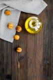 Масло как косметики Масло грецкого ореха около грецкого ореха в ореховой скорлупе на темном деревянном космосе экземпляра взгляд  Стоковое Изображение