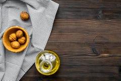 Масло как косметики Масло грецкого ореха около грецкого ореха в ореховой скорлупе на темном деревянном космосе экземпляра взгляд  Стоковая Фотография