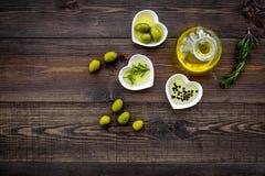 Масло на кухонном столе Дополнительное виргинское оливковое масло в стеклянном опарнике около зеленых оливок и ветви розмариновог Стоковое Изображение