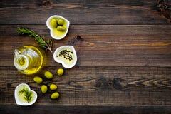 Масло на кухонном столе Дополнительное виргинское оливковое масло в стеклянном опарнике около зеленых оливок и ветви розмариновог Стоковые Фотографии RF