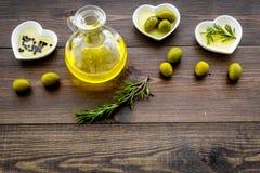 Масло на кухонном столе Дополнительное виргинское оливковое масло в стеклянном опарнике около зеленых оливок и ветви розмариновог Стоковые Изображения