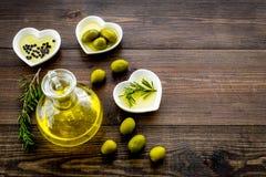 Масло на кухонном столе Дополнительное виргинское оливковое масло в стеклянном опарнике около зеленых оливок и ветви розмариновог Стоковое Изображение RF