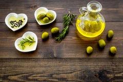 Масло на кухонном столе Дополнительное виргинское оливковое масло в стеклянном опарнике около зеленых оливок и ветви розмариновог Стоковое фото RF