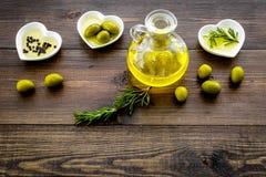 Масло на кухонном столе Дополнительное виргинское оливковое масло в стеклянном опарнике около зеленых оливок и ветви розмариновог Стоковая Фотография RF