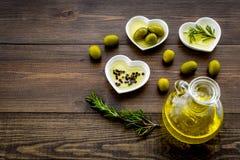 Масло на кухонном столе Дополнительное виргинское оливковое масло в стеклянном опарнике около зеленых оливок и ветви розмариновог Стоковые Фото