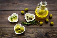 Масло на кухонном столе Дополнительное виргинское оливковое масло в стеклянном опарнике около зеленых оливок и ветви розмариновог Стоковая Фотография