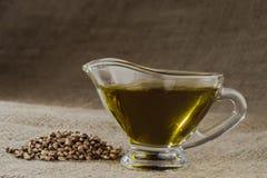 Масло пеньки в стеклянной шлюпке подливки и пригорошня семян конопли на предпосылке мешковины стоковое фото