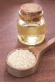 Масло сезама в стеклянных семенах опарника и сезама на деревянной ложке - indicum Sesamum Стоковое Изображение RF