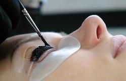 масло состава красотки ванны мылит обработку Cosmetologist кладет черную краску на плетки прокатывая ресницы Взгляд верхней грани Стоковое фото RF