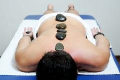 массажа человека кровати камни горячего ослабляя стоковые фото