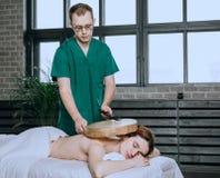 Массажируйте заднюю часть женщины с тамбурин Нетрадиционные методы медицины Красивая расслабленная сторона молодой женщины стоковая фотография