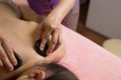 Массажируйте терапевта кладя камни курорта на задней части девушки лежа на таблицу массажа стоковое фото rf