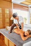 Массаж задней части женщины курорта масло состава красотки ванны мылит обработку Тело, терапия заботы кожи Стоковая Фотография