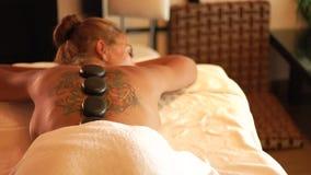 Массаж наслаждения молодой женщины горячий каменный в салоне спа красоты Каменная терапия массажа обработки и тела Дзэн и ослабит видеоматериал