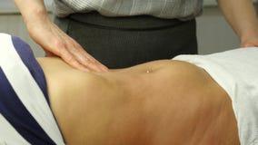 Массаж Anticellulite в клинике руки конца-вверх masseur делая подбрюшный массаж, массаж внутренних органов 4K сток-видео