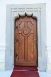 Массивнейшая деревянная дверь, художнические бетонные стены и вход красного ковра Стоковые Фото