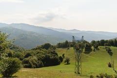 Массивнейший поляк электричества в природе, зеленая вегетация покрыл горы в предпосылке высоковольтный штендер электричества Стоковые Изображения RF