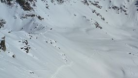 Массивный холм горы предусматриванный в снеге, группа людей идет, воздушный отснятый видеоматериал в 4k сток-видео