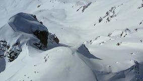 Массивный холм предусматриванный в снеге с человеком взбираясь он, от высокого угла в 4k акции видеоматериалы