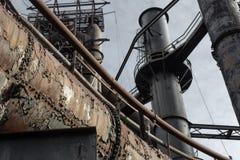 Массив заклепанных труб и дымовых труб, подиумов и лестниц промышленного места стоковые фотографии rf