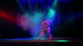 Мастерская предпосылка карате с покрашенным дымом выполняет kata видеоматериал