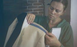 Мастерская ремесла для портняжничать Молодая белошвейка ремонтируя куртку людей светлую, измеряя размеры на манекене Тонизировать стоковые фото