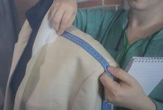 Мастерская ремесла для портняжничать Молодая белошвейка ремонтируя куртку людей светлую, измеряя размеры на манекене Тонизировать стоковое фото