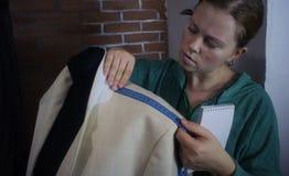 Мастерская ремесла для портняжничать Молодая белошвейка ремонтируя куртку людей светлую, измеряя размеры на манекене Тонизировать стоковая фотография rf